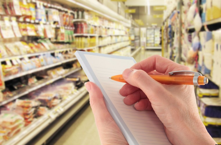 Hand with Pen Writing a Shopping List in a Supermarket